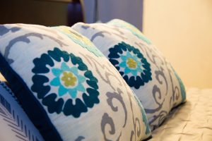 blue and teal pillows on bed at a corporate rental apartment - choose to be happy