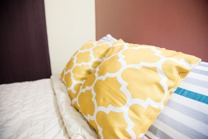 yellow pillows on decorate bed at the westbury vacation rental - choose to be happy